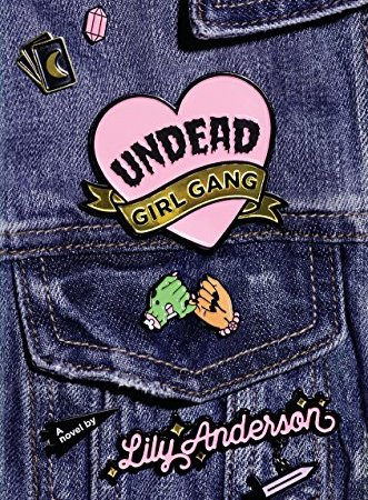 "A close-up of a denim jacket with pins on it. The pins show a knife, a crystal, Tarot cards, and two hands making a pinky-swear. One hand has brown skin and one has green skin like a zombie. The pins include the text: ""Undead Girl Gang. A novel by Lily Anderson."""