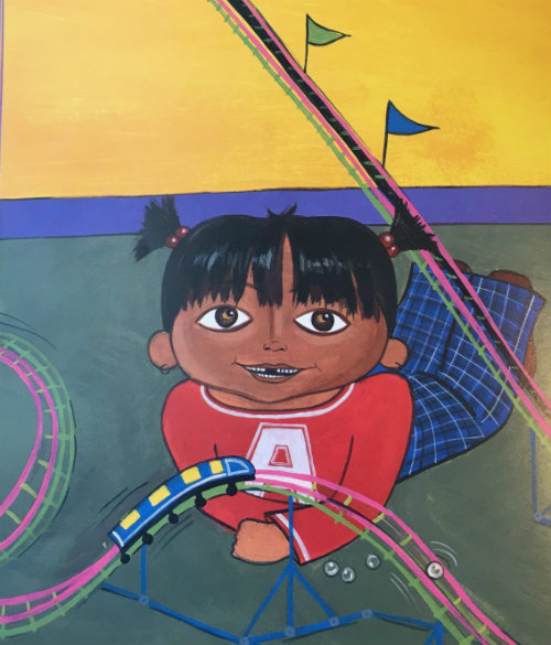 Anu has brown skin and black hair in pigtails. She wears a red shirt and blue plaid pants. She lies on the floor smiling with a toy rollercoaster in front of her.