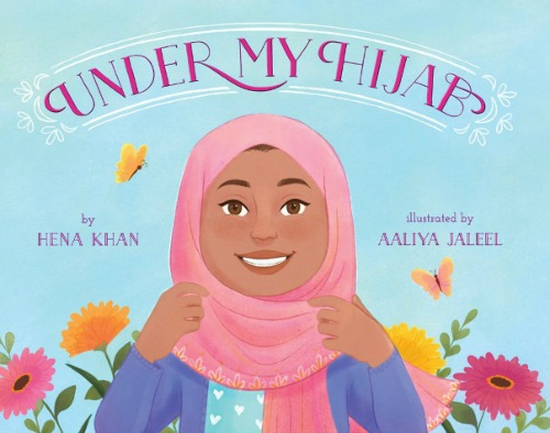 "A young girl with brown skin smiles and adjusts her pink hijab. She wears a blue shirt with white polka dots and a purple sweater. The background is light blue with flowers and butterflies. Pink text: ""Under My Hijab by Hena Khan illustrated by Aaliya Jaleel."""