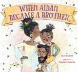 "Image: A pregnant mother kisses the forehead of a young boy, who sits on his father's shoulders. All three family members have brown skin and black hair. A white and yellow cat looks on. Text: ""When Aidan Became a Brother. By Kyle Lukoff. Illustrated by Kaylani Juanita."""